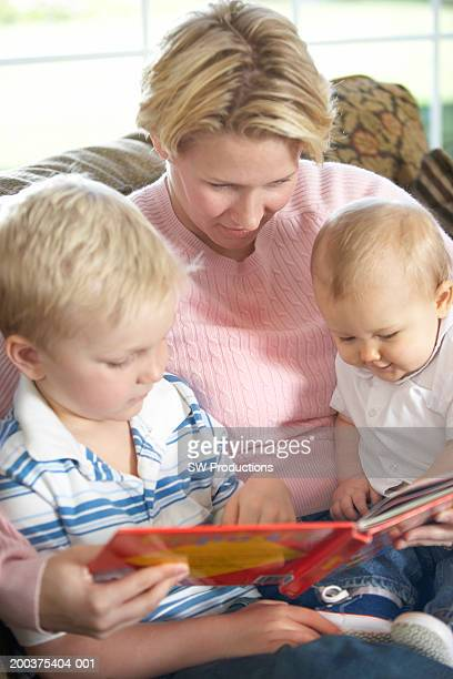 mother reading to baby girl (8-11 months) and boy (4-6) on sofa - 6 11 months stock pictures, royalty-free photos & images