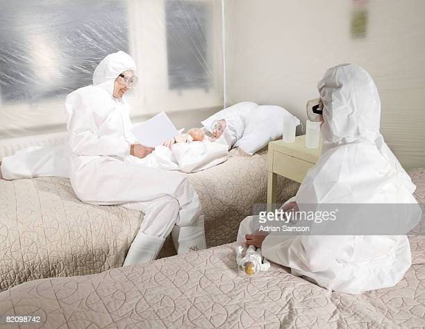 Mother reading to children in protective suits