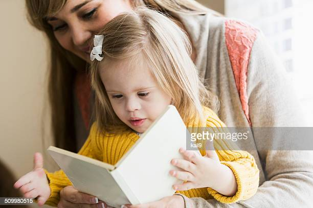 mother reading to daughter with down syndrome - down syndrome stock pictures, royalty-free photos & images