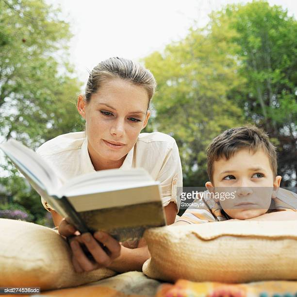 mother reading to her bored son (10-11) - 10 11 years stock photos and pictures
