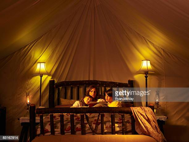 Mother reading to her children in bed inside tent.