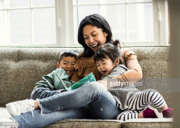 mother reading to kids on couch - family with two children stock photos and pictures