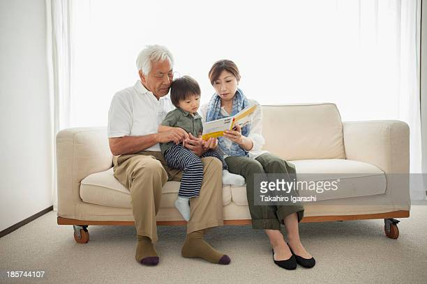 Mother reading to son sitting on grandfather's lap