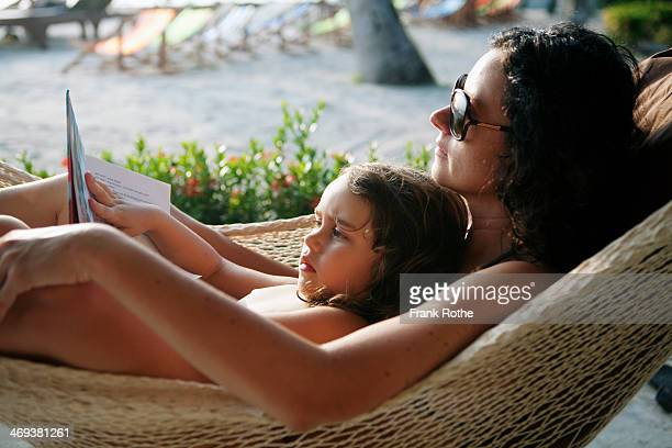 mother reads a book to here child in a hammock