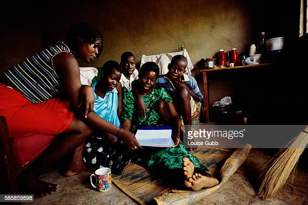 A mother reads a memory book with her children The mother a victim of AIDS created the book for her children as part of a project organized by the...