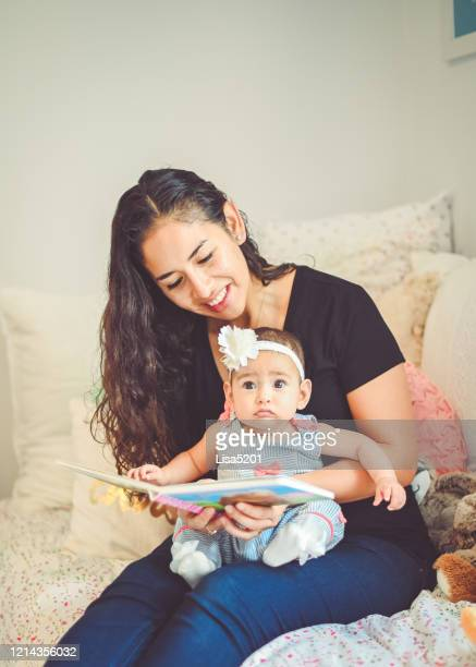 mother reads book to sweet 6 month old baby - puerto rican ethnicity stock pictures, royalty-free photos & images