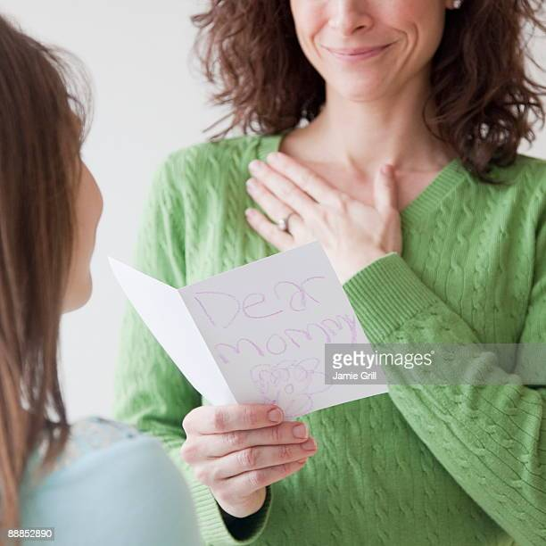 Mother receiving greeting card on mothers day from daughter (10-11 years)
