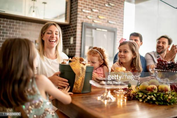 mother receiving presents of her daughter at home on christmas time - amigo secreto - anniversary stock pictures, royalty-free photos & images