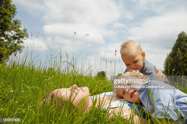 Mother relaxing with children in grass
