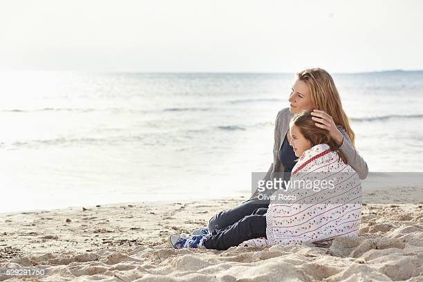 mother relaxing with daughter (7-9) on beach - avvolto in una coperta foto e immagini stock