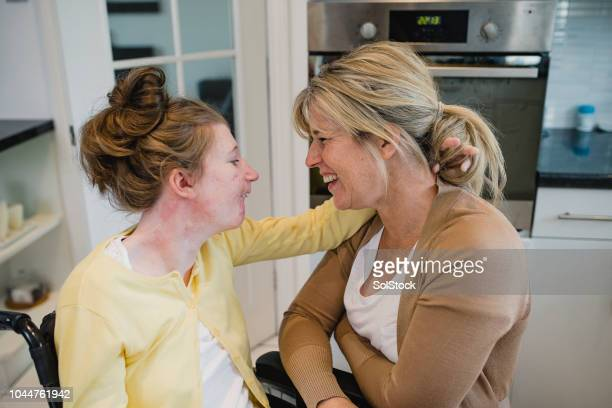mother relaxing with disabled daughter at home - learning disability stock pictures, royalty-free photos & images