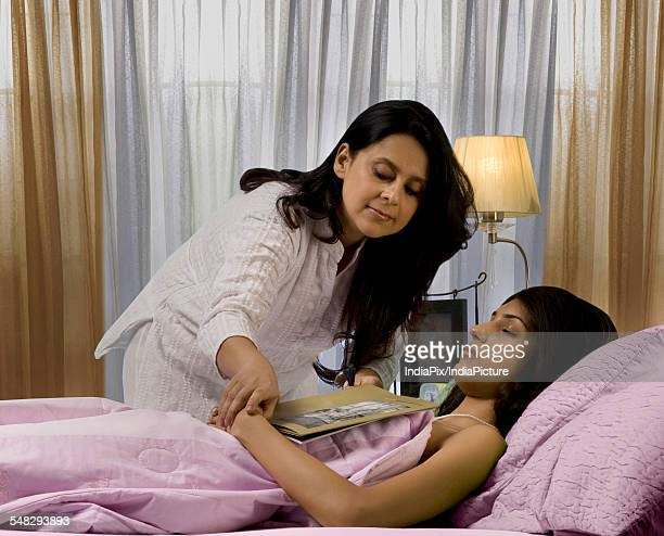 Mother removing a book from her daughters clutches