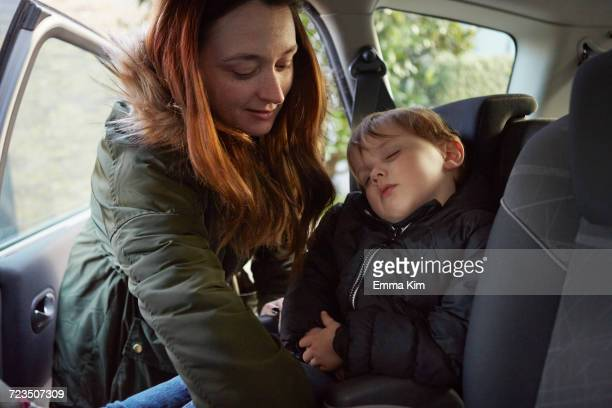 Mother removing sleeping toddler son from car backseat