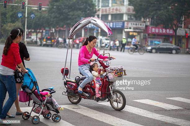 A mother rides an ebike with her baby sitting on the innovative baby seat China now has an in excess of 130 million ebikes on its town and city roads...