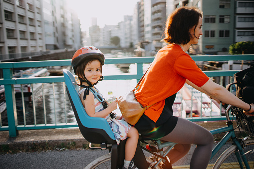 Mother riding a bicycle with a toddler girl in urban city, Tokyo - gettyimageskorea
