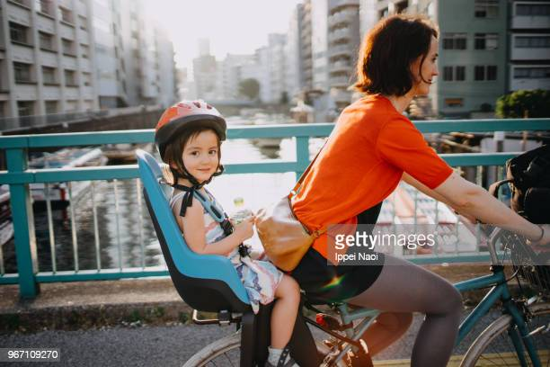 Mother riding a bicycle with a toddler girl in urban city, Tokyo