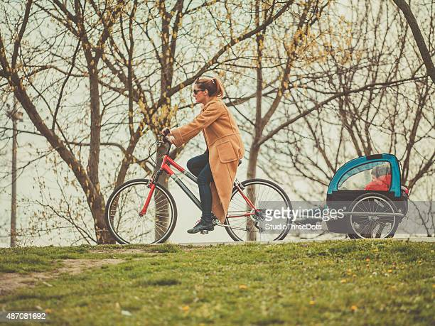 mother riding a  bicycle with her kids on trailer - trailer stock pictures, royalty-free photos & images