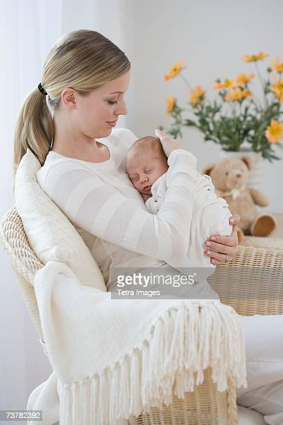 Mother rocking newborn baby in chair