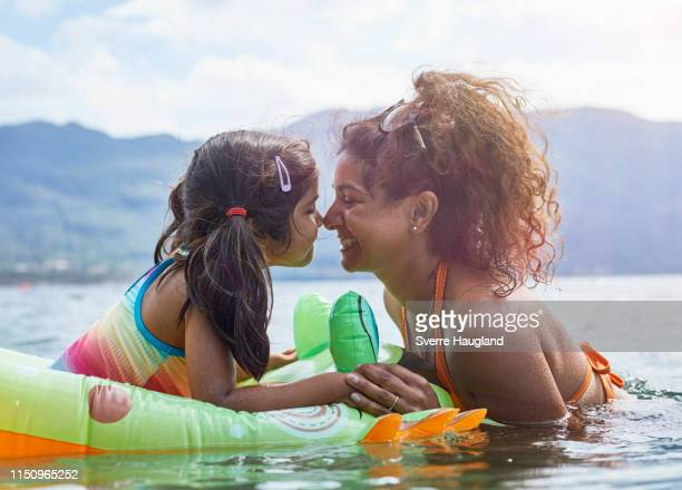 mother rubbing noses with daughter on inflatable frog in lake - india summer fotografías e imágenes de stock