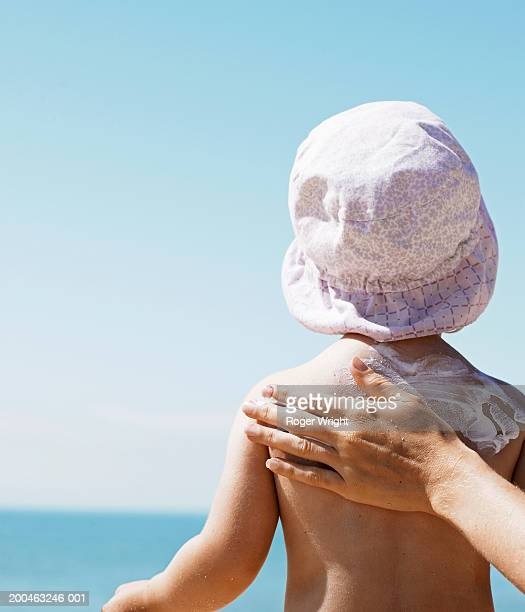 Mother rubbing suncream on daughter (1-3) on beach, rear view
