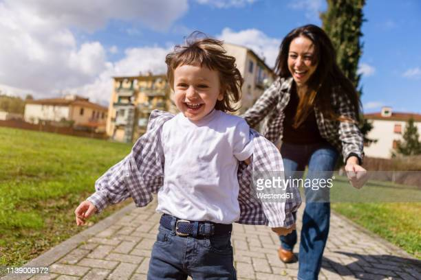 mother running behind happy toddler son on a path - 追いかける ストックフォトと画像