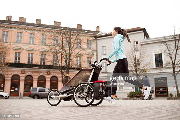 mother running with child in stroller in the city - cochecito para niños fotografías e imágenes de stock