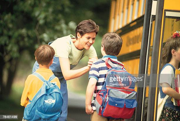 Mother saying goodbye to kids by school bus