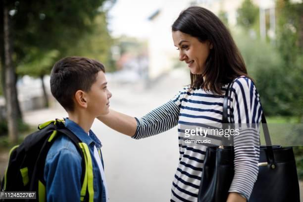 mother saying goodbye to son in front of school - mamma e figlio foto e immagini stock