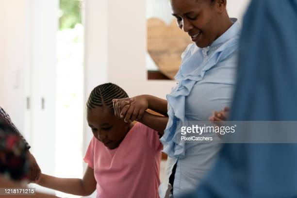 mother saying grace holding daughters hand - religious blessing stock pictures, royalty-free photos & images