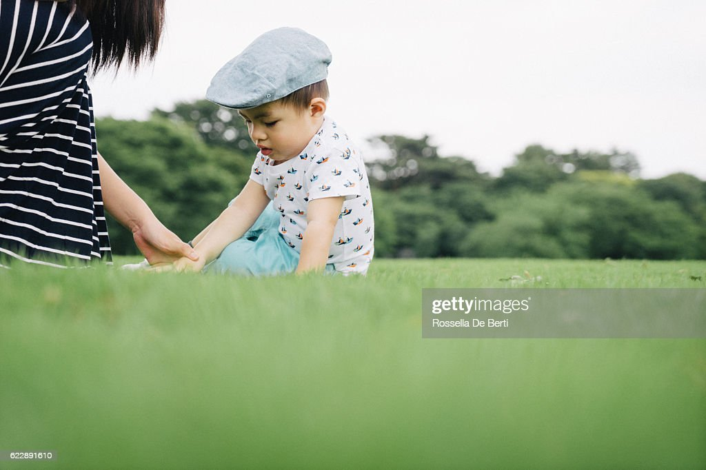 Mother scolding her son outdoors in a park : Stock Photo