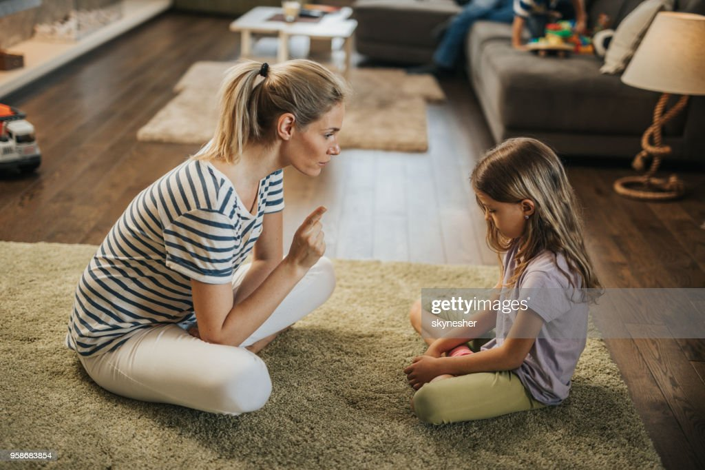 Mother scolding little girl on carpet in the living room. : Stock Photo