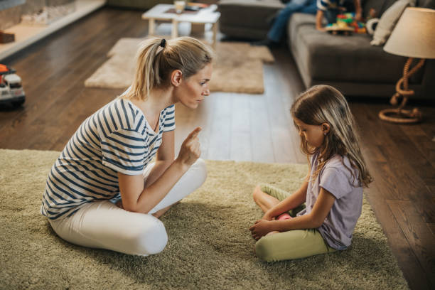 mother scolding little girl on carpet in the living room. - parents angry stock pictures, royalty-free photos & images