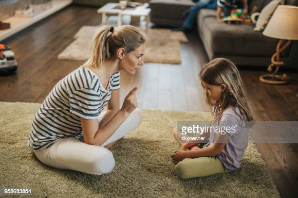 mother scolding little girl on carpet in the living room. - censura imagens e fotografias de stock