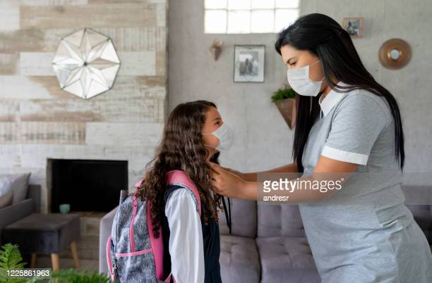 mother sending her girl to school wearing a facemask in the middle of the covid-19 pandemic - reopening stock pictures, royalty-free photos & images