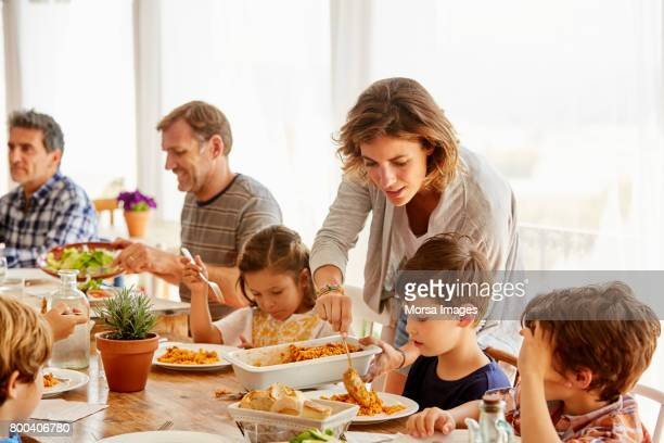 mother serving food to children against window - lunch stock pictures, royalty-free photos & images