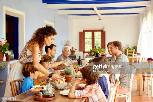 mother serving food to children at table - almoço imagens e fotografias de stock