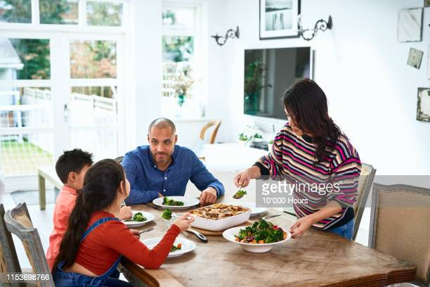 mother serving fresh healthy food to children and husband - four people stock pictures, royalty-free photos & images