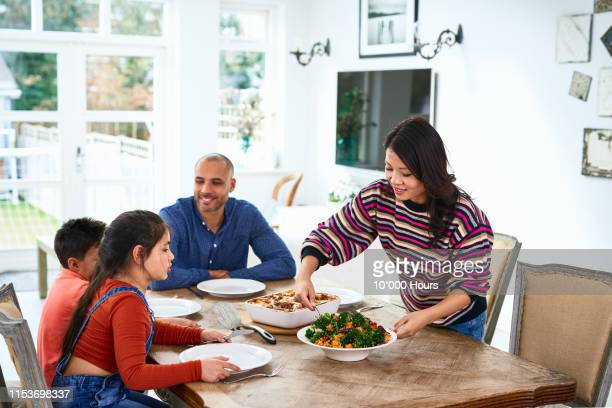 mother serving home made food for family and smiling - filipino family dinner stock pictures, royalty-free photos & images