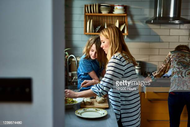 mother serving lunch with daughter in kitchen - lifestyles stock pictures, royalty-free photos & images