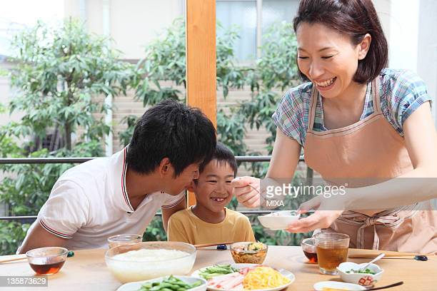 Mother serving meal to father and son
