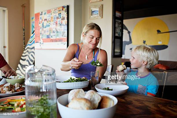 Mother serving salad for her son
