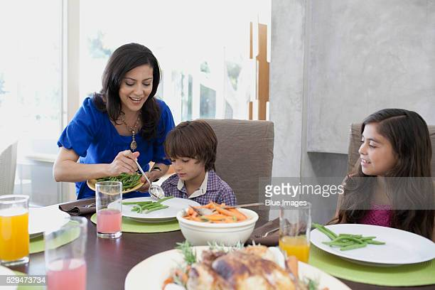 mother serving son green beans - serving food and drinks stock pictures, royalty-free photos & images