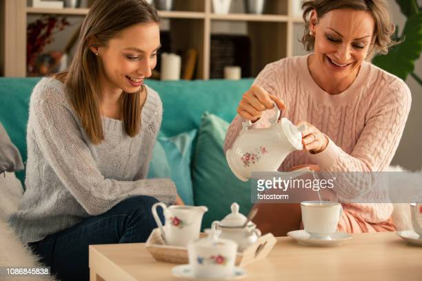 mother serving tea to her daughter - afternoon tea stock pictures, royalty-free photos & images