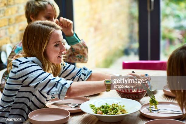mother serving vegan lunch at dining table - lgbtq  and female domestic life fotografías e imágenes de stock