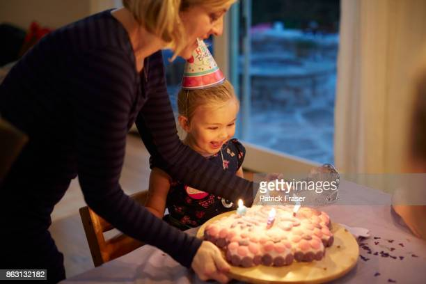 mother sets birthday cake in front of smiling little girl - birthday candles stock photos and pictures