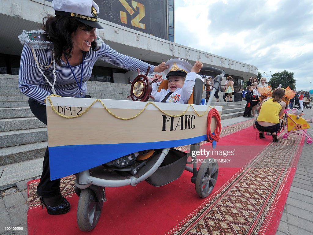 A mother sets straight a hat of her son sitting in a pram made like a ship during the First Festival of Prams in Kiev on May 21, 2010.