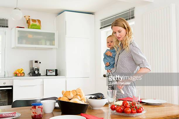 Mother setting kitchen table while holding baby daughter