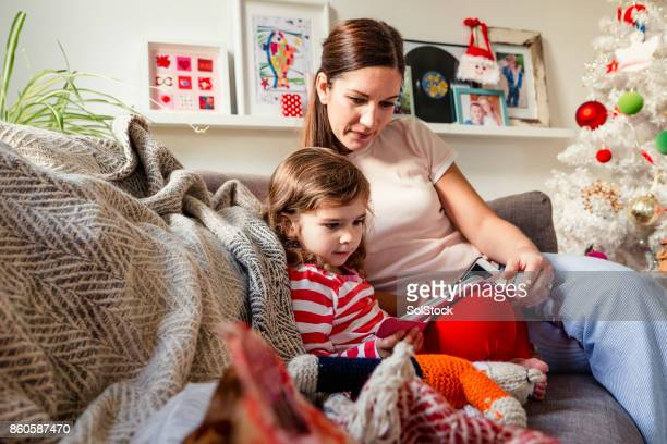 mother sharing a digital tablet with her little girl - happy new month stock photos and pictures