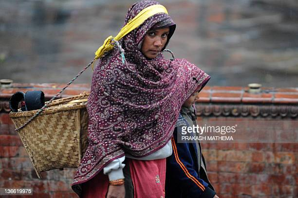A mother shelters her son from the rain at Basantapur Durbar Square in Kathmandu on January 9 2012More than 10 people died due to cold wave in...