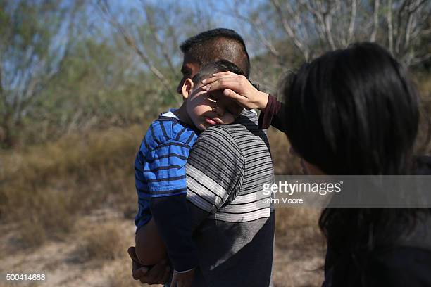 A mother shields the face of her son's from the sun as her husband carries their sleeping boy after their family illegally crossed the USMexico...